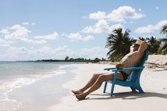 Hombre en silla en la playa de Caribbian Fotos de archivo libres de regalías
