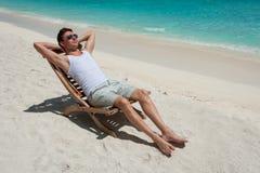 Hombre en silla que toma el sol en la playa cerca del mar Fotos de archivo libres de regalías