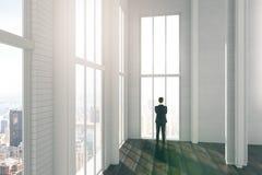 Hombre en sitio ligero grande del desván con la opinión de la ciudad y el flo de madera Fotos de archivo