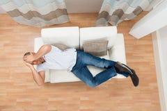 Hombre en Sofa Having Headache foto de archivo libre de regalías