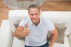 Hombre en Sofa Showing Thumbs Up Fotos de archivo
