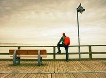 Hombre en sombrero con la mochila que viaja, turista en el reloj del puente al mar Imagen de archivo libre de regalías