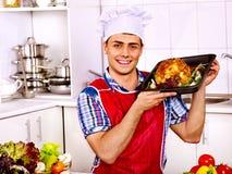 Hombre en sombrero del cocinero que cocina el pollo Foto de archivo