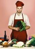 Hombre en sombrero del cocinero y delantal con la ensalada El cocinero trabaja en cocina con las verduras y las herramientas Fotos de archivo