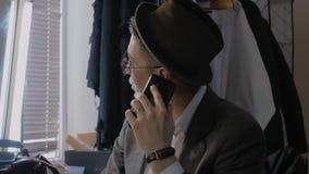 Hombre en sombrero que habla en el teléfono almacen de metraje de vídeo