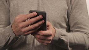 Hombre en suéter que charla en el teléfono en el fondo blanco Gente y communoication almacen de metraje de vídeo