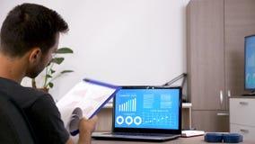Hombre en su sala de estar que comprueba datos de empresa en cartas animadas almacen de metraje de vídeo