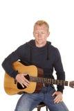Hombre en sudadera con capucha con mirada de la guitarra abajo Fotos de archivo