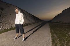 Hombre en sudadera con capucha en el camino abandonado Imagenes de archivo