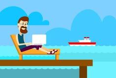 Hombre en Sunbed usando la isla tropical del océano de la playa del ordenador portátil de trabajo remoto del lugar de verano del  Imagen de archivo