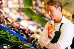 Hombre en supermercado como ayudante de departamento Fotos de archivo libres de regalías