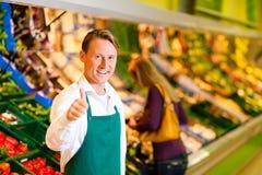Hombre en supermercado como ayudante de departamento Foto de archivo
