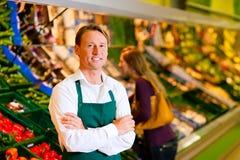 Hombre en supermercado como ayudante de departamento Imágenes de archivo libres de regalías