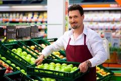 Hombre en supermercado como ayudante de departamento Imagen de archivo libre de regalías