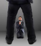 Hombre en sus rodillas que ruega para no ser despedido Fotografía de archivo