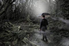 Hombre en técnicas mixtas de niebla del bosque Fotografía de archivo