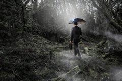 Hombre en técnicas mixtas de niebla del bosque Imagen de archivo