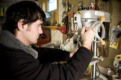 Hombre en taller usando el taladro Fotos de archivo libres de regalías