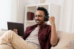 Hombre en teléfonos con PC de la tableta que escucha la música Imagen de archivo