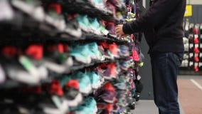 Hombre en tienda de zapatos del deporte almacen de metraje de vídeo