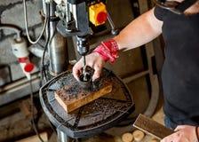 Hombre en trabajo sobre la prensa de taladro eléctrico Fotografía de archivo libre de regalías