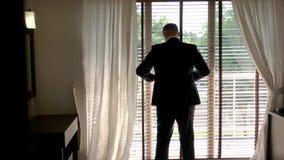 Hombre en traje cerca de la ventana metrajes