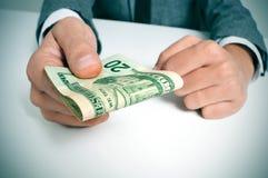 Hombre en traje con un taco de billetes de dólar americanos Foto de archivo libre de regalías