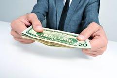 Hombre en traje con un taco de billetes de dólar americanos Imagen de archivo libre de regalías