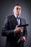 Hombre en traje de negocios con un arma Foto de archivo