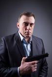 Hombre en traje de negocios con un arma Fotos de archivo libres de regalías