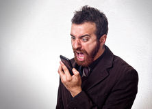 Hombre en traje de negocios que grita en su teléfono móvil Imagenes de archivo