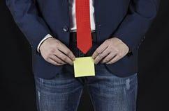 Hombre en traje, hombre de negocios que lleva a cabo la etiqueta engomada en su área de la ingle, fondo negro, prostatitis foto de archivo libre de regalías