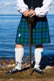 Hombre en traje escocés con la espada Fotos de archivo libres de regalías