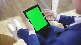 Hombre en traje formal azul usando su tableta para leer el periódico en línea metrajes