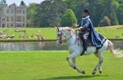 Hombre en traje isabelino con la espada en un caballo que galopa delante de hogar majestuoso Imagenes de archivo