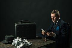 Hombre en traje mafia Fabricación del dinero Transacción del dinero Trabajo del hombre de negocios en oficina del contable concep imagen de archivo