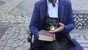 Hombre en traje retro en el banco que mira tiempo en su pocketwatch almacen de video