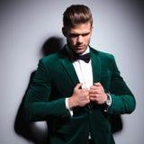 Hombre en traje verde y la corbata de lazo que miran un poco triste Fotos de archivo