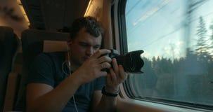 Hombre en tren que escucha la música y que hace la cantidad almacen de metraje de vídeo