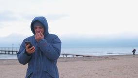 Hombre en un azul abajo de la chaqueta en la playa de la arena por el mar que mecanografía un mensaje por las manos congeladas en metrajes