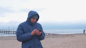 Hombre en un azul abajo de la chaqueta en la playa de la arena por el mar que mecanografía un mensaje en el teléfono móvil almacen de metraje de vídeo