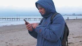 Hombre en un azul abajo de la chaqueta en la playa de la arena por el mar que mecanografía un mensaje en el teléfono móvil Vista  almacen de video