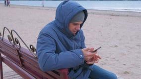 Hombre en un azul abajo de la chaqueta que se sienta en un banco en la playa de la arena y que mecanografía un mensaje en el telé metrajes