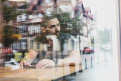 Hombre en un café que refleja en vidrio Vida de ciudad Foto de archivo