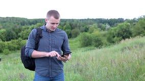 Hombre en un campo con la tableta digital almacen de metraje de vídeo