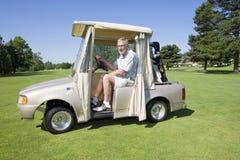 Hombre en un carro de golf fotos de archivo