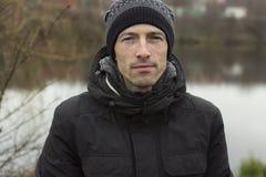 Hombre en un casquillo hecho punto y un jacketr negro imágenes de archivo libres de regalías