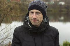Hombre en un casquillo hecho punto y un jacketr negro foto de archivo
