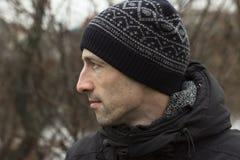 Hombre en un casquillo hecho punto y un jacketr negro fotografía de archivo