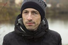 Hombre en un casquillo hecho punto y un jacketr negro imagen de archivo